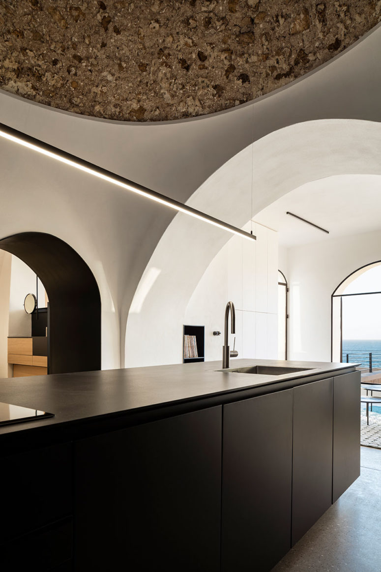 The kitchen is black and white, with a large kitchen island and additional light everywhere
