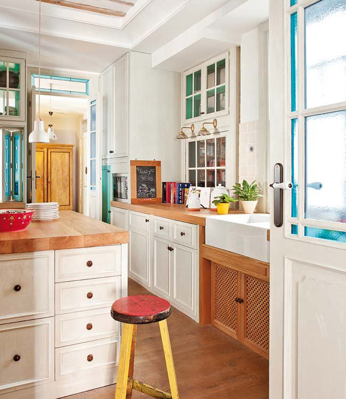 The kitchen is vintage meets mid-century modern, with traditional white cabinets and warm wood counters