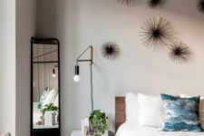 07 the master bedroom is personalized with unique wall decor and industrial wall lamps