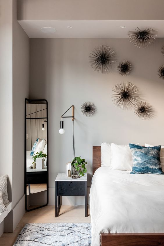 the master bedroom is personalized with unique wall decor and industrial wall lamps