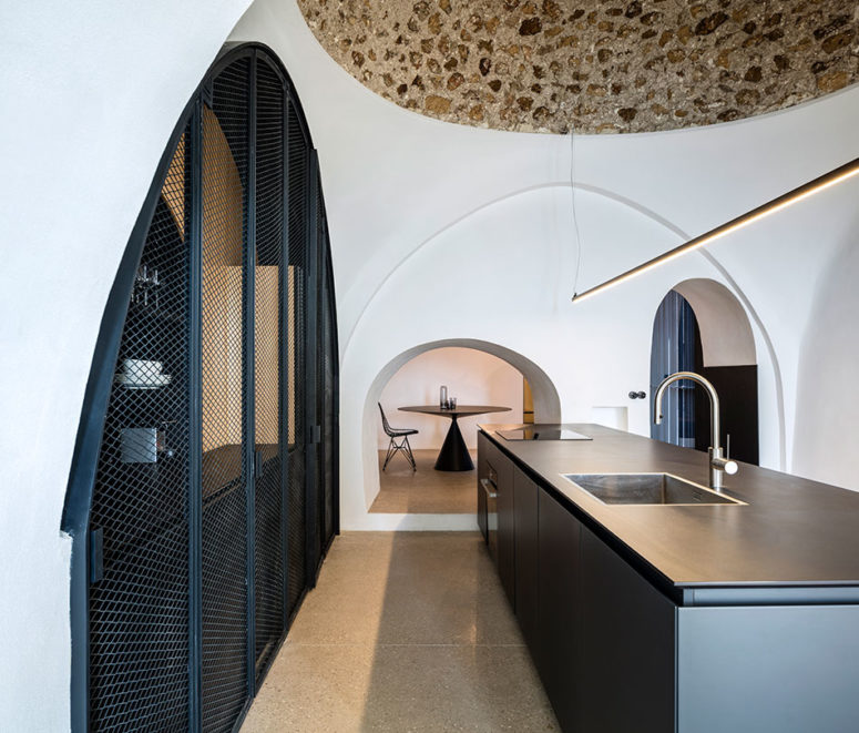 The ancient stone ceilings are neighboring with modern metal net doors and minimalist lights