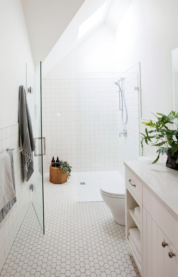 The bathroom is clad with white tiles, square and hexagon ones, there's a cute wooden stool right in the shower
