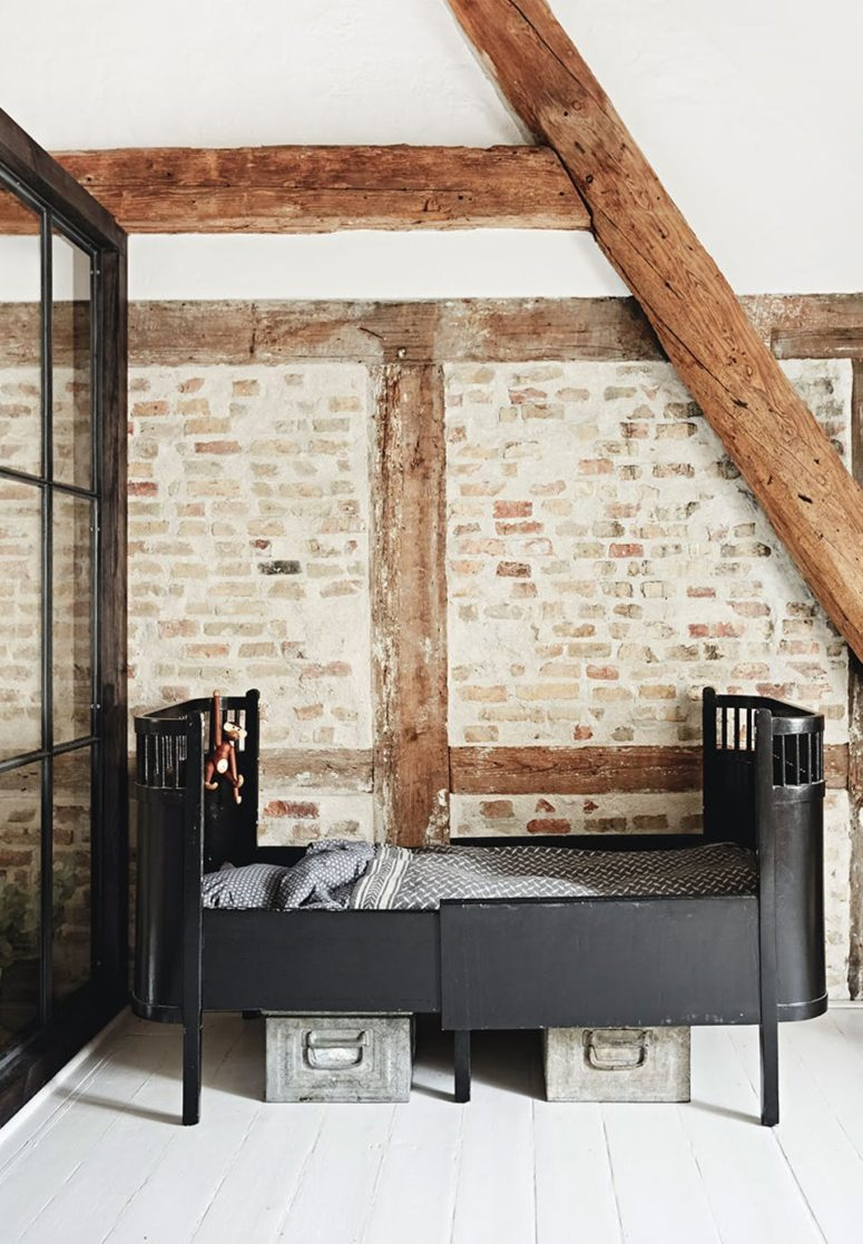 The kid's room is a boy's space, there are beams and brick walls and a vintage metal bed, a metal box under the bed is used for storage