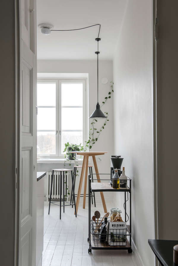 The kitchen is all-white, with tall stools, greenery and a metal bar cart for an industrial feel