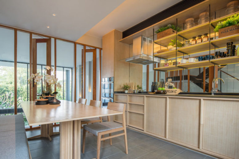The kitchen is fully clad in light-colored wood, which makes it cozy and inviting and a glazed wall fills it with light