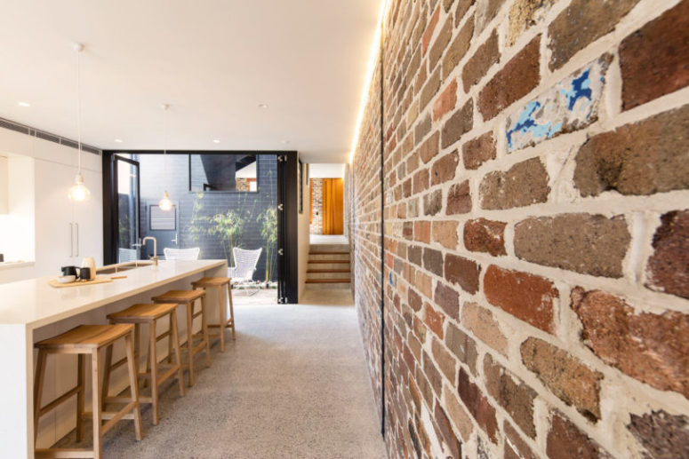 The kitchen is minimalist and industrial, with brick walls and sleek white furniture and kitchen island