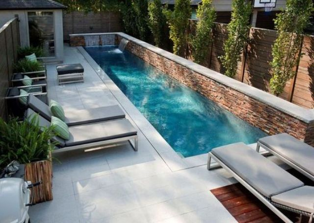 a modern small backyard with a narrow pool with waterfall and a couple of  loungers