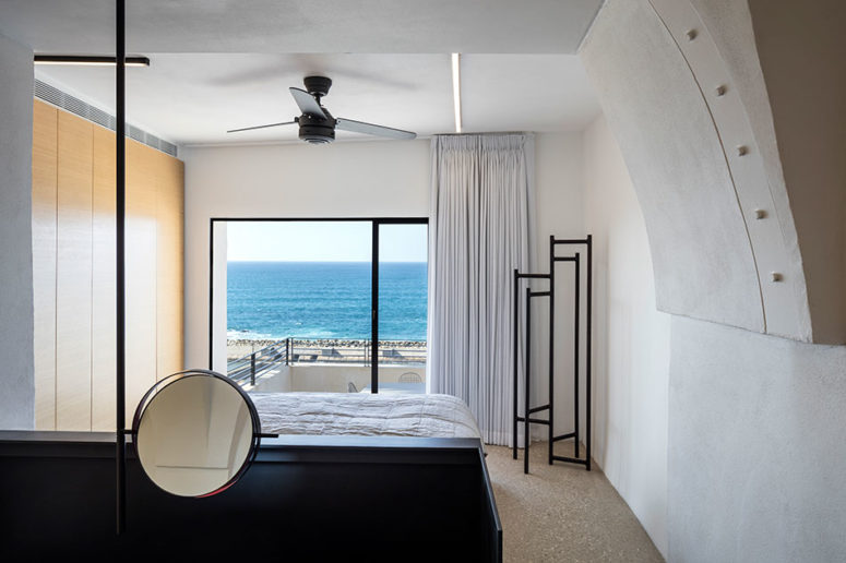 The bedroom is white, with a black bed, eye-catchy black clothes rack and a light veneer wardrobe, the sea view is amazing
