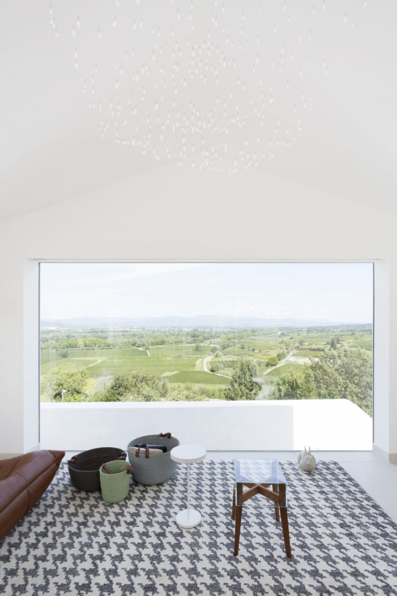 The chandelier of many little bulbs and a patterned rug are pieces of interest here but nothing distract attention from the views