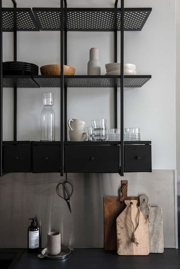 The kitchen cabinets and countertops are made of blackened metal, the shelves have a ligthweight look due to the perforated design
