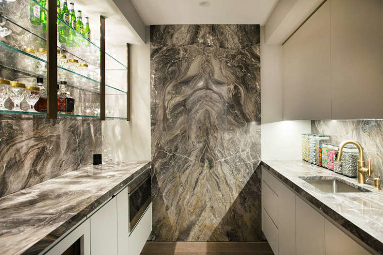 The kitchen is done with dark marble and there's a large glass home bar