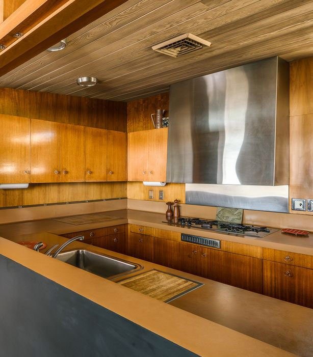 The kitchen is fully clad with amber colored natural wood and stainless steel touches stand out a lot