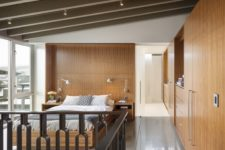 09 The master bedroom is clad with warm-colored wood and there's a glazed wall to catch the views
