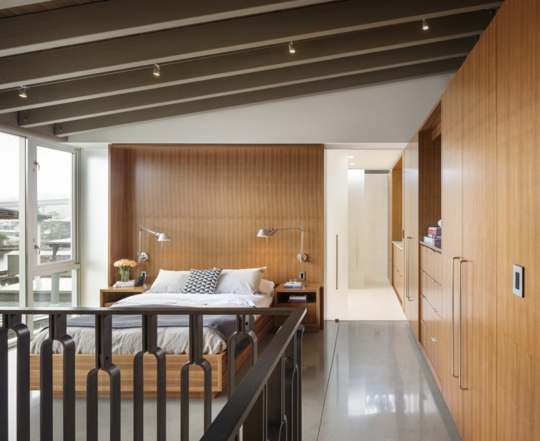 The master bedroom is clad with warm-colored wood and there's a glazed wall to catch the views