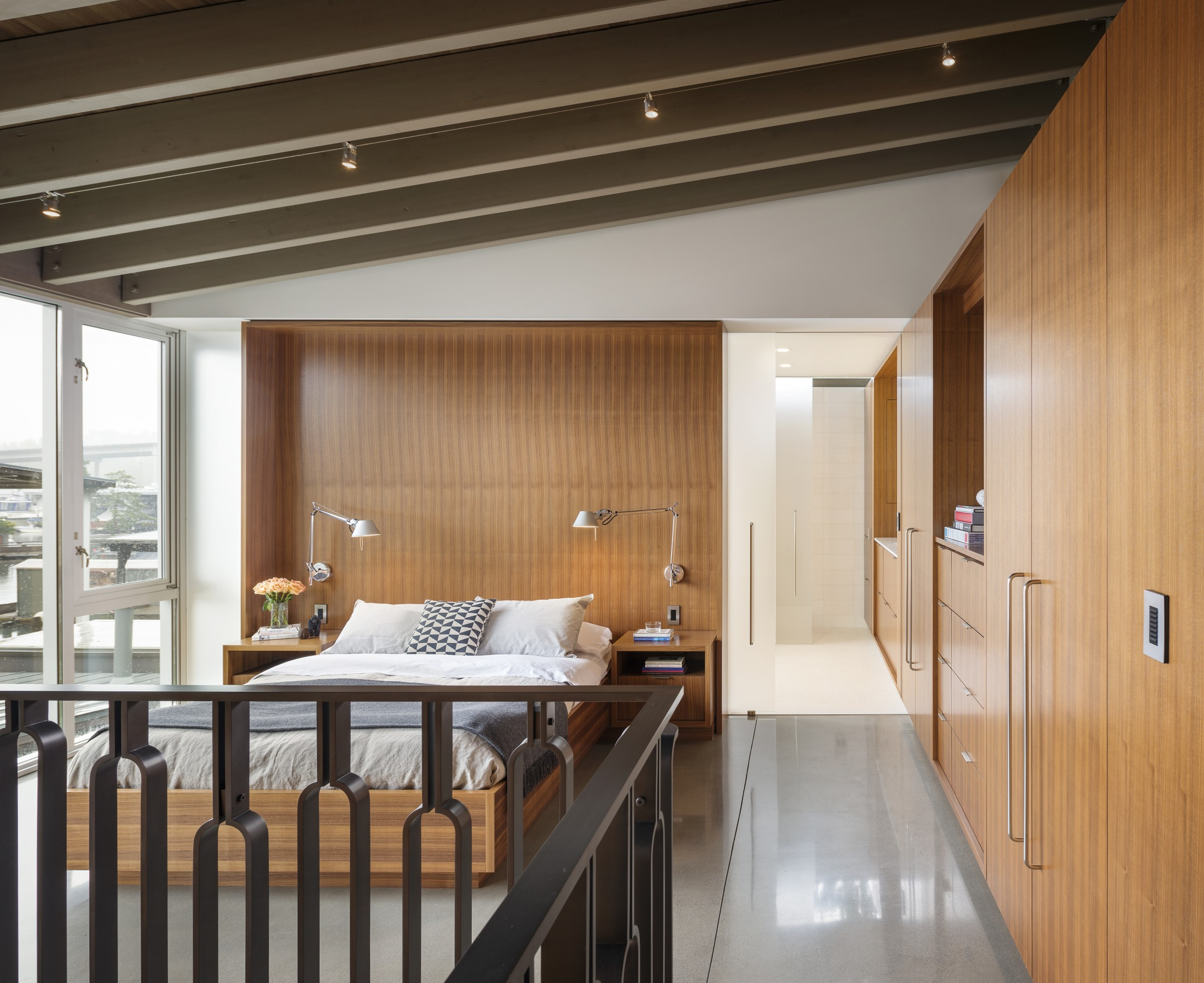 The master bedroom is clad with warm colored wood and there's a glazed wall to catch the views