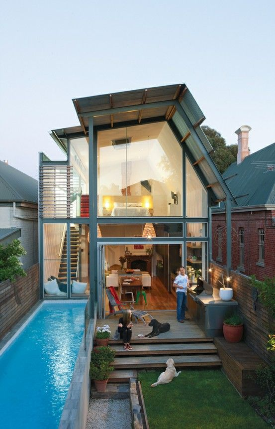 a leveled backyard with a lawn and a narrow pool uses the whole space effectively