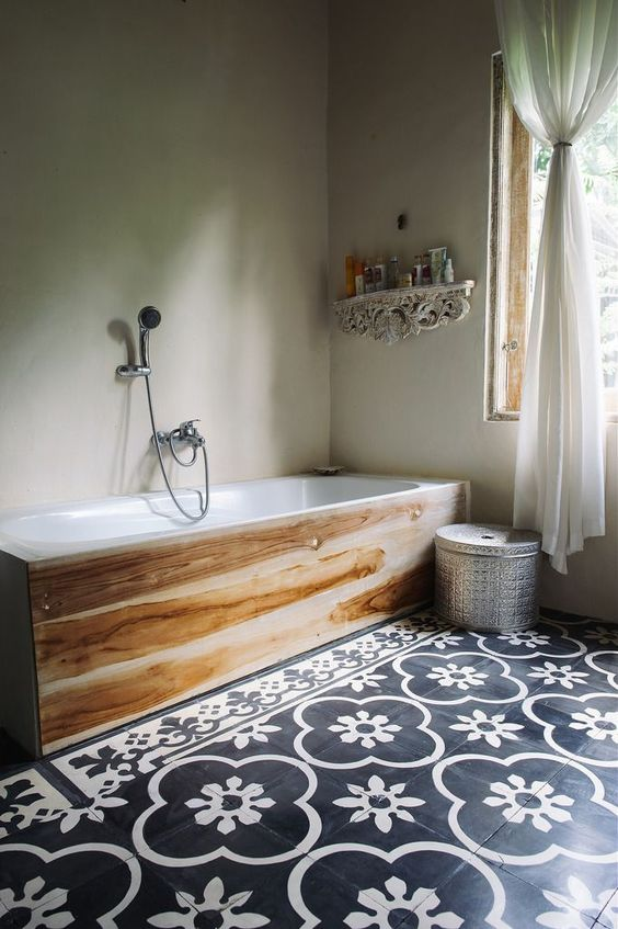 black and white patterned floor tiles and a wood covered bathtub