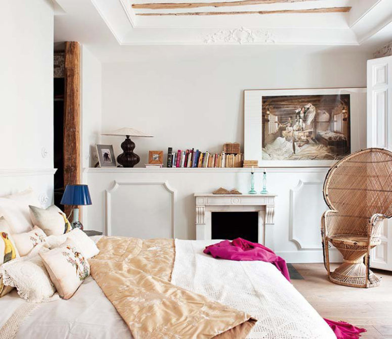 the bedroom is personalized with a large artwork, a fireplace and a wicker chair of a cool shape