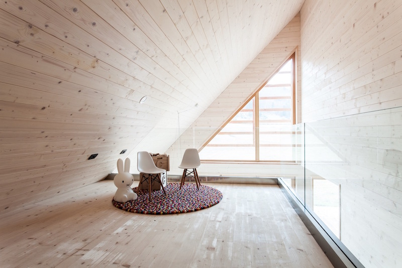 The attic ceiling definitely makes the space feel smaller but it also gives it a cozy feel