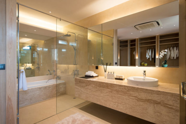 The bathroom is clad with light-colored stone, there's a shower and a bathtub