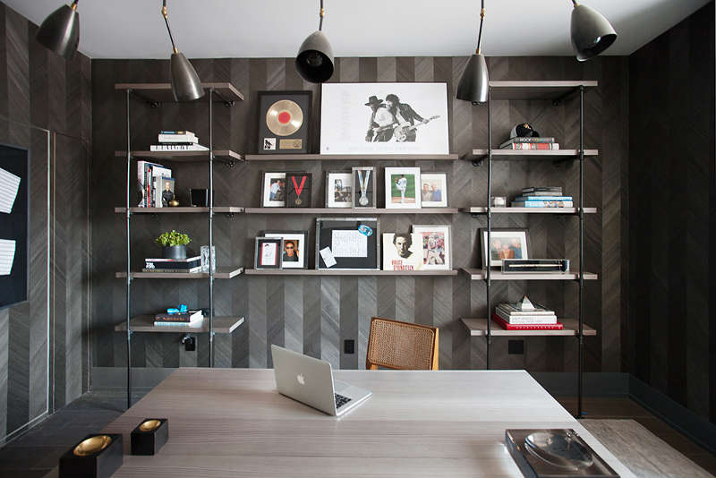 The home office is dark and moody, with unique wallpaper imitating reclaimed wood clad in a chevron pattern