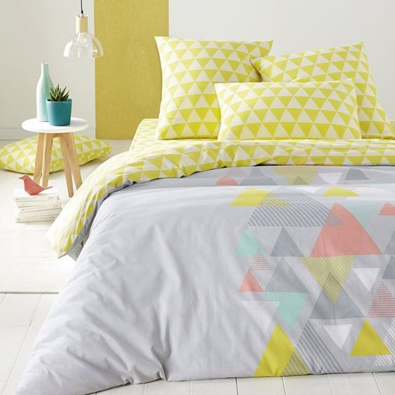 a grey duvet with some muted colored triangles and lime triangle print pillowcases