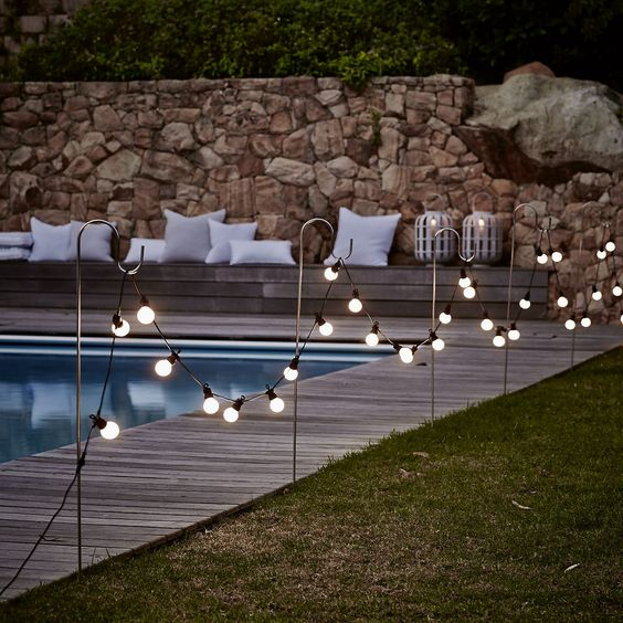bistro bulb fairylights attached to hooks along the whole pool