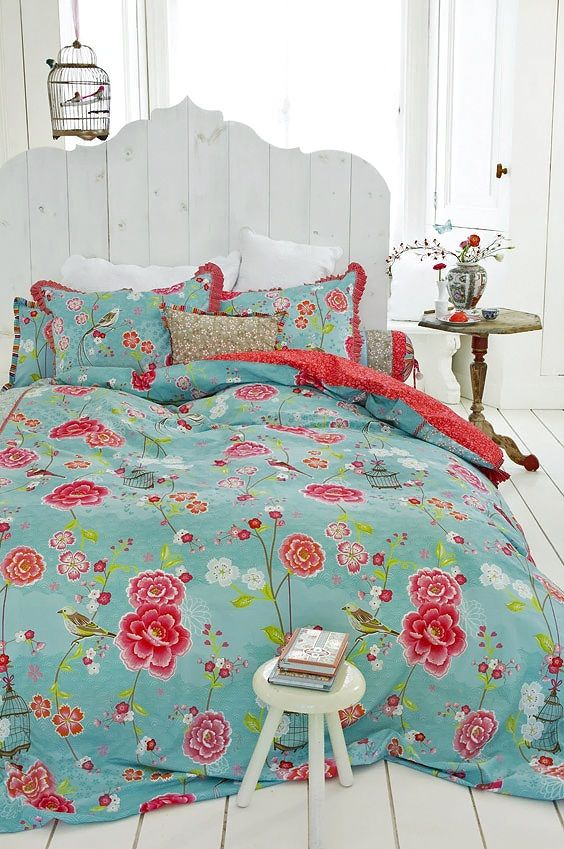 blue bedding with red and fuchsia flowers and red ruffles on the pillowcases