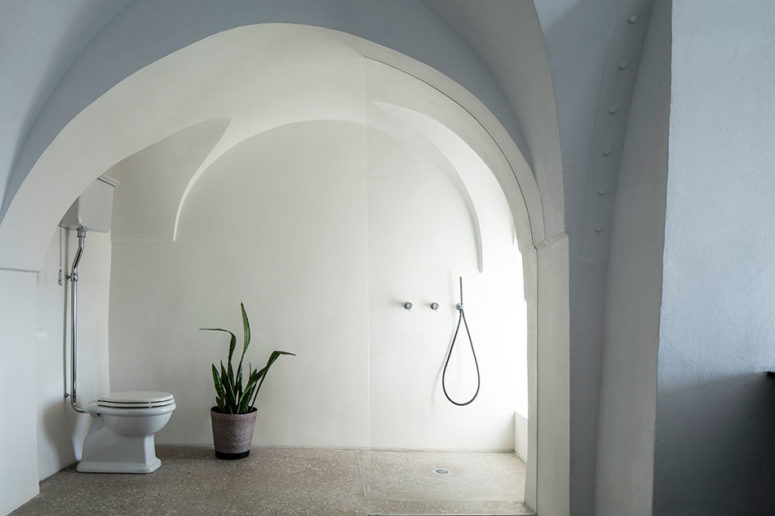 The bathroom is also minimalist, with a seamless glass shower