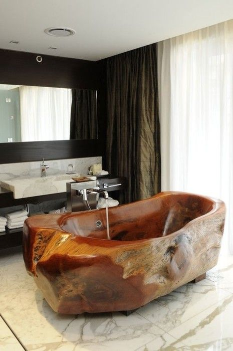 a rough carved stone bathroom makes a bold statement in this elegant marble bathroom