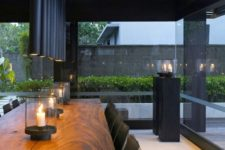 15 black tube lamps over the table echo with the shutters and make the space moody