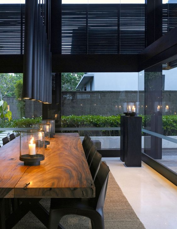 black tube lamps over the table echo with the shutters and make the space moody