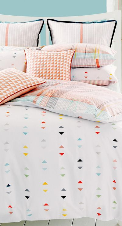 pastel checked bedding with colorful triangle prints on the duver and some pillowcases