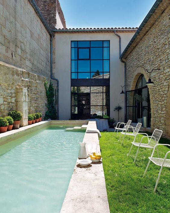 a small backyard with a lawn and a narrow pool clad with tiles