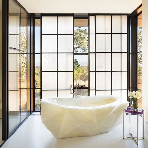 gorgeous faceted tub carved from white onyx is a wow-factor in this bathroom