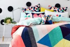 22 colorful hexagon print pillows and a bold duvet with colorful geo figures on it