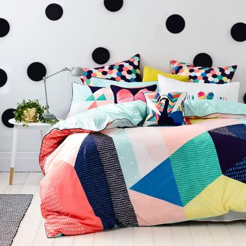 colorful hexagon print pillows and a bold duvet with colorful geo figures on it