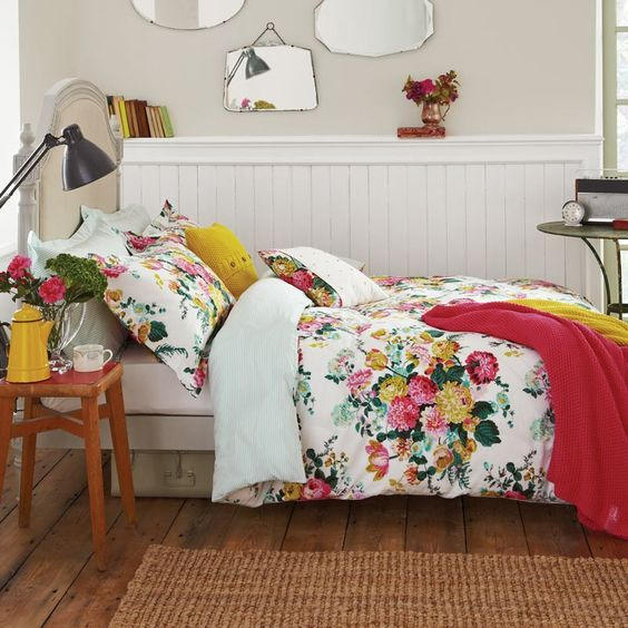 red and yellow floral bedding with accnet pillows and blankets in matching colors