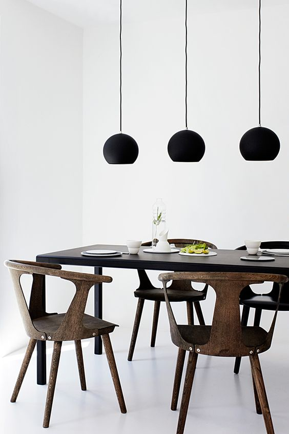 this minimalist dining space is highlighted with matte black pendant lamps