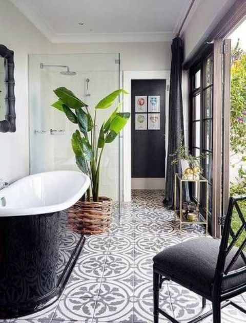 a palm tree in a woven pot enlivens a black and white bathroom