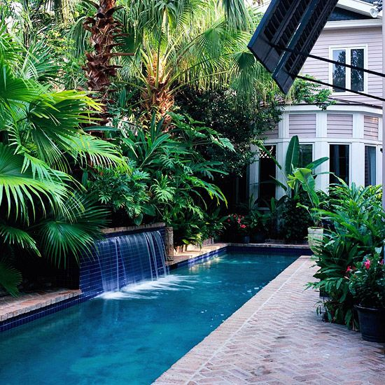brick clad backyard with a lot of greenery for privacy and a narrow pool with waterfalls
