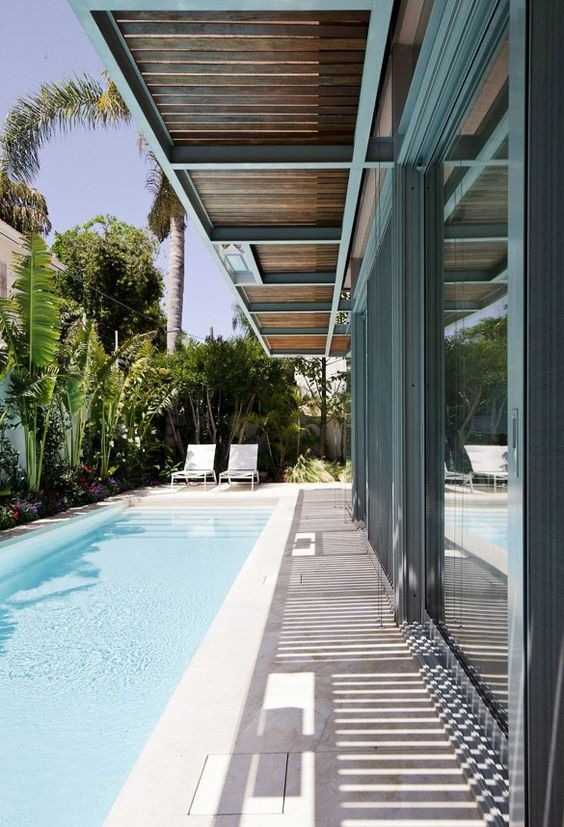 long lap pool along the whole side of the house, it's clad with stone-like concrete
