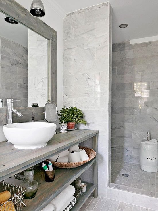 grey bathroom is enlivened with a single potted plant