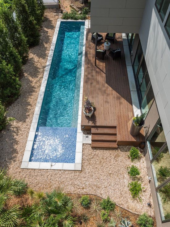 narrow backyard pool clad with white tiles next to a wooden deck