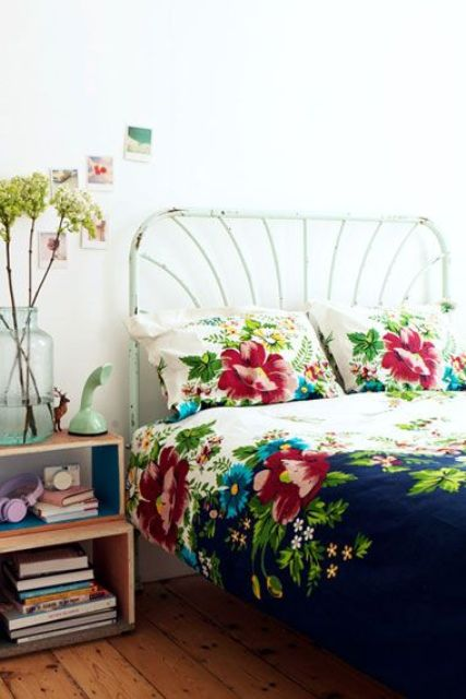 vintage-inspired navy and cream bedding with bold turquoise and red flowers on it