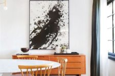 29 a black and white splatter artwork in a mid-century modern dining space