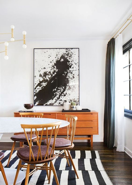 a black and white splatter artwork in a mid-century modern dining space