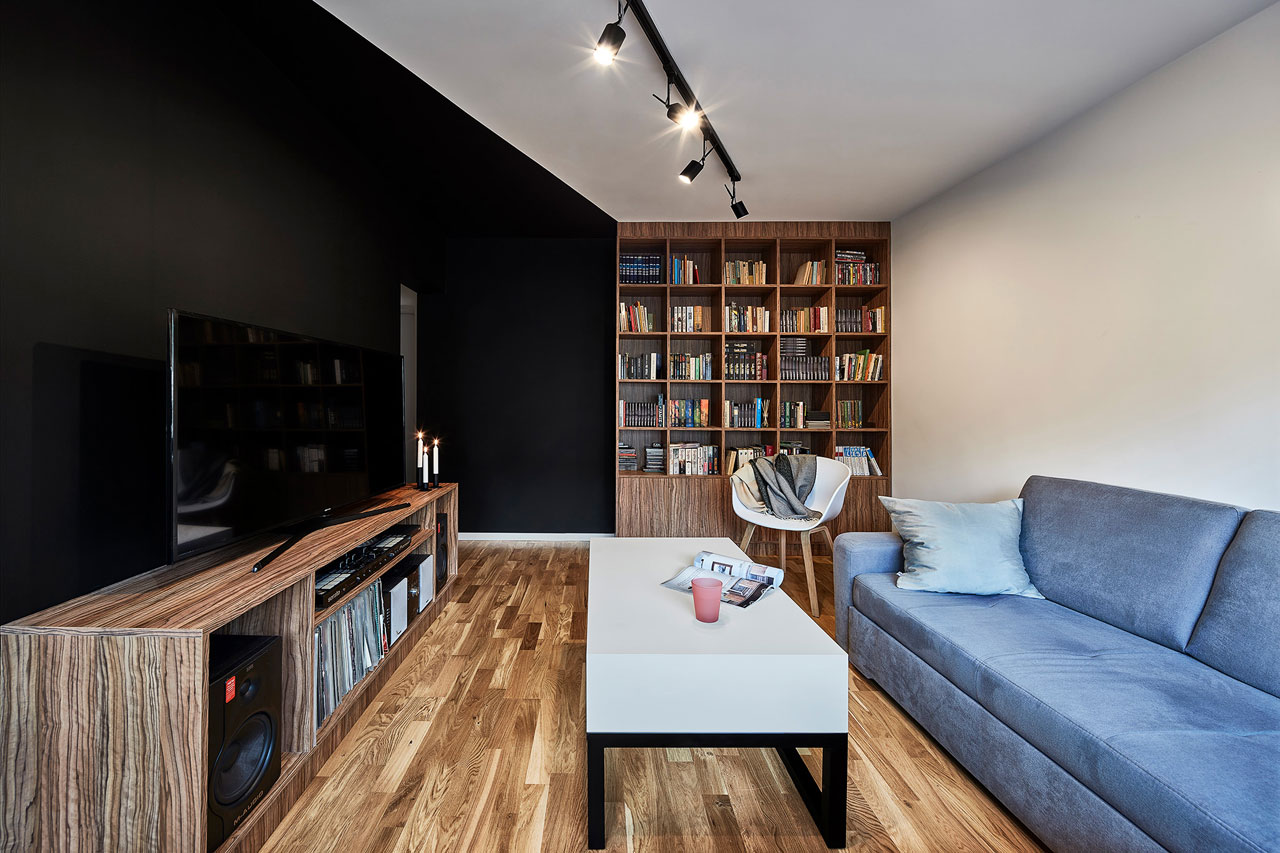 This compact Polish apartment is done in black and white with warm colored wooden touches that make it cozier and welcoming