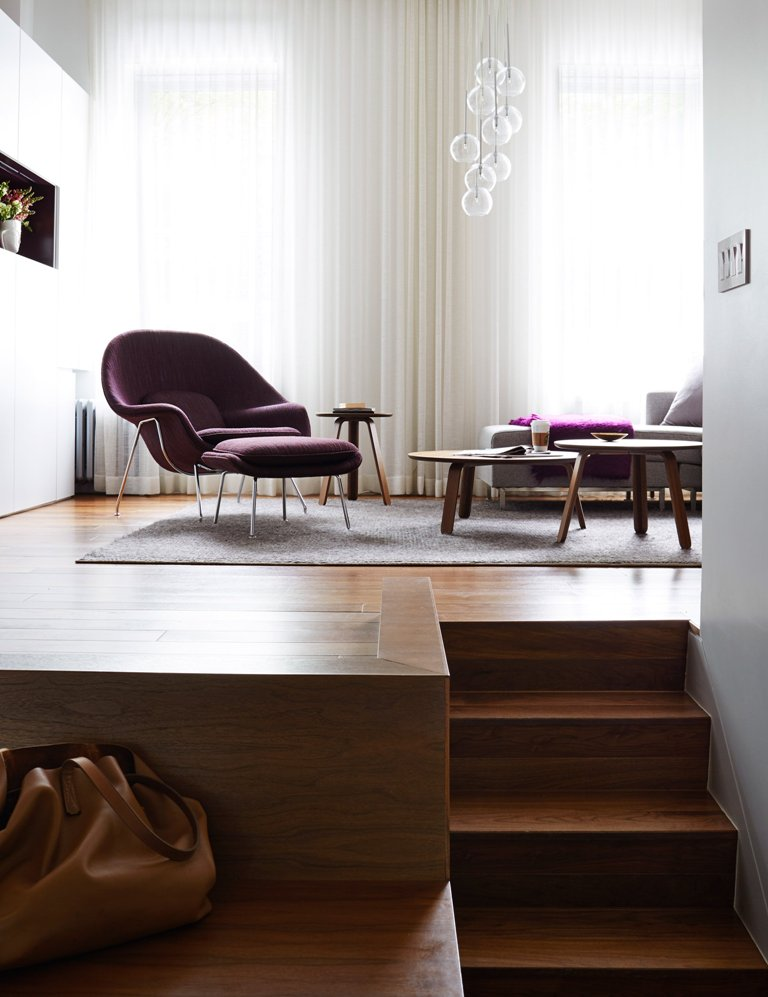 Most of the apartment is done in creamy and neutral shades, with grey furniture and a rug and some purple furniture for an accent