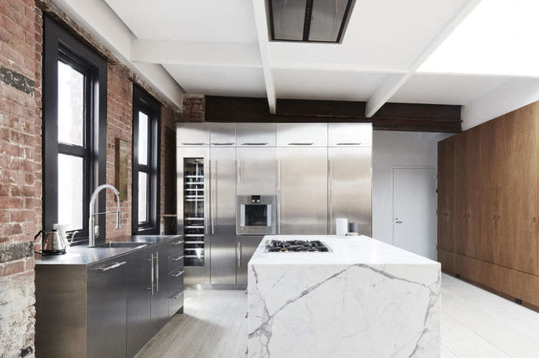 The kitchen features stainless steel cabinets, wooden tall ones for storage and a large marble kitchen island